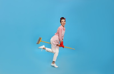 Young housewife with broom having fun on light blue background
