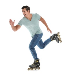 Handsome young man with inline roller skates on white background