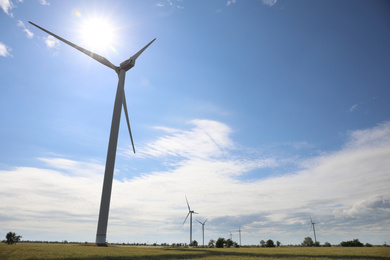 Field with wind turbines, low angle view. Alternative energy source