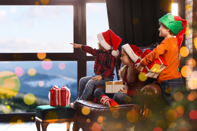 Little children waiting for Santa Claus near window indoors. Christmas holiday