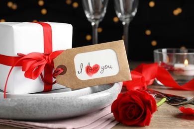 Beautiful place setting and tag with phrase I Love You on table against blurred lights, closeup. Valentine's day romantic dinner