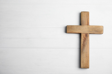 Christian cross on white wooden background, top view with space for text. Religion concept