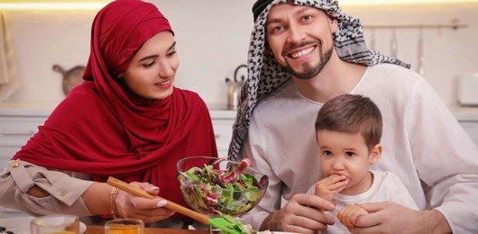 Happy Muslim family eating together at table in kitchen. Banner design