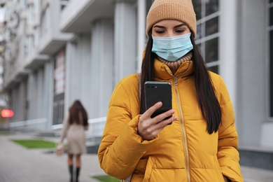 Young woman in medical face mask with smartphone walking outdoors. Personal protection during COVID-19 pandemic