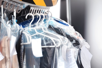 Hangers with clothes on garment conveyor at dry-cleaner's, closeup
