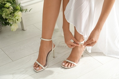 Young bride in wedding dress putting on shoes indoors, closeup