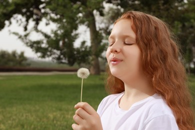 Cute girl with beautiful red hair blowing dandelion in park, space for text. Allergy free concept