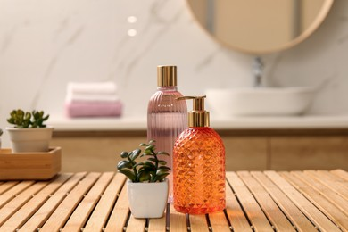 Glass dispenser with liquid soap, bottle of gel and plants on wooden table in bathroom