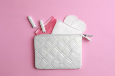 Bag with menstrual pads, tampons and pantyliners on pink background, flat lay