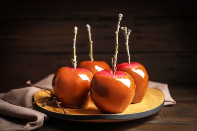 Plate with delicious caramel apples on wooden table