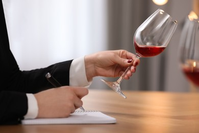 Sommelier tasting wine at table indoors, closeup