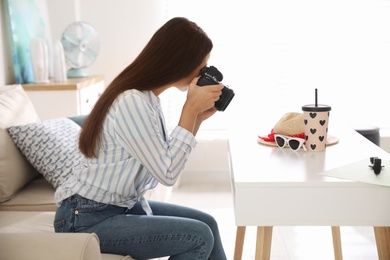 Young photographer taking picture of accessories indoors