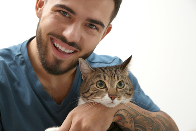 Happy man with cat at home. Friendly pet