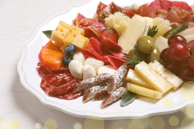 Plate full of assorted appetizers on white table, closeup