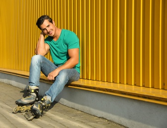 Handsome young man with inline roller skates sitting near yellow building, space for text