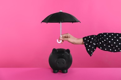 Woman holding small umbrella over piggy bank on pink background, closeup