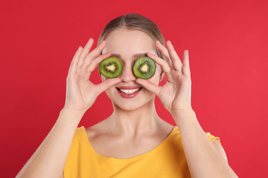 Young woman with cut kiwi on red background. Vitamin rich food