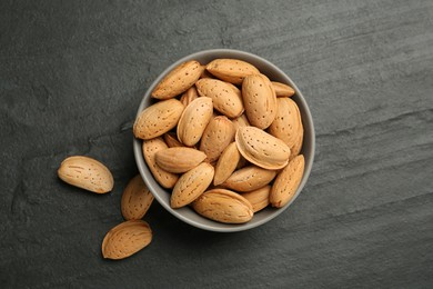 Ceramic bowl with almonds on black table, flat lay. Cooking utensil