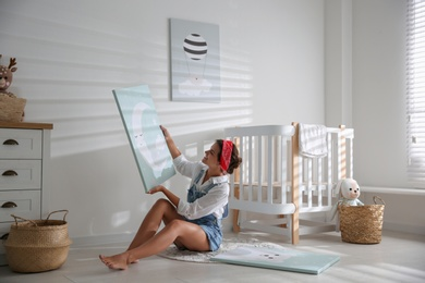 Decorator with picture on floor in baby room. Interior design