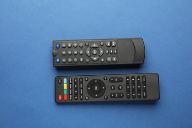 Different remote controls on blue background, flat lay