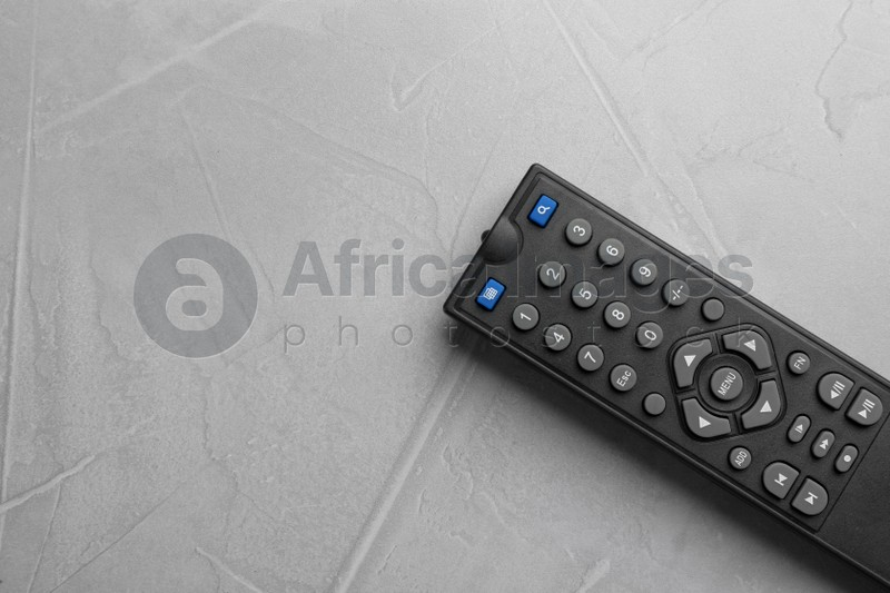 Modern tv remote control on grey table, top view. Space for text