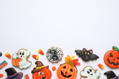 Tasty cookies and sweets for Halloween party on white table, flat lay. Space for text