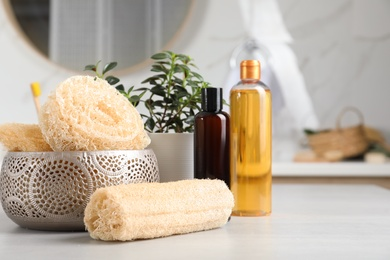 Natural loofah sponges and personal hygiene products on table in bathroom
