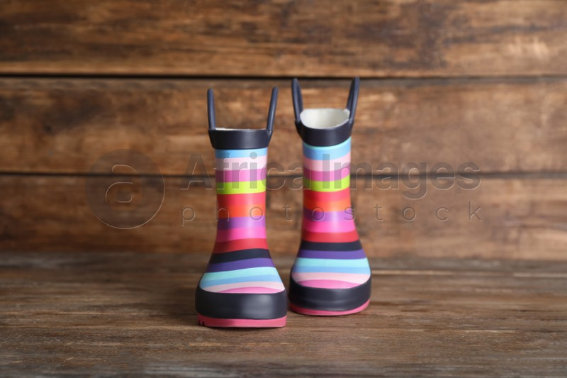 Pair of striped rubber boots on wooden surface