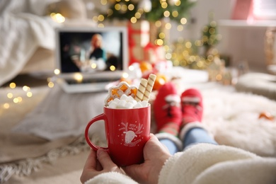MYKOLAIV, UKRAINE - DECEMBER 25, 2020: Woman with sweet drink watching The Queen's Gambit series on laptop at home, closeup. Cozy winter holidays atmosphere