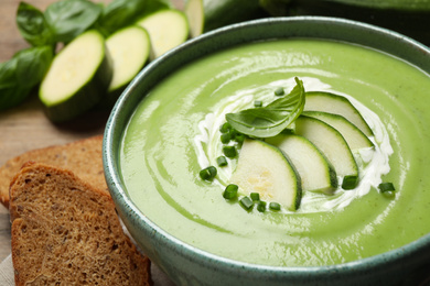 Tasty homemade zucchini cream soup in bowl on table, closeup