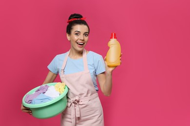 Housewife holding bottle of cleaning product and basin with clothes on pink background, space for text