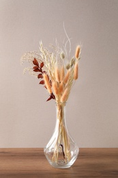 Dried flowers in vase on wooden table against light background