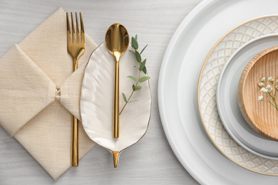 Elegant cutlery with green leaves on table, flat lay. Festive setting