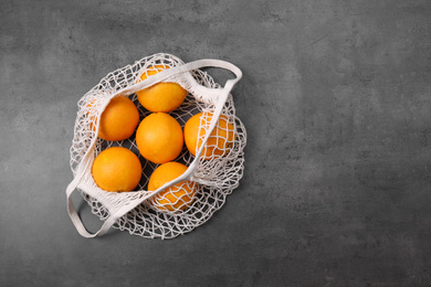 Net bag with oranges on grey table, top view. Space for text