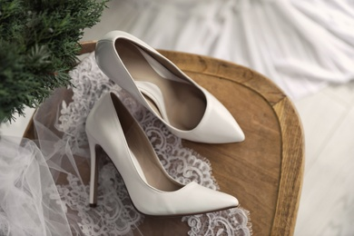 Pair of white high heel shoes, veil and wreath on wooden chair indoors, above view. Dressing for wedding