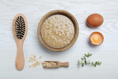 Homemade hair mask in bowl, ingredients and brush on white wooden table, flat lay