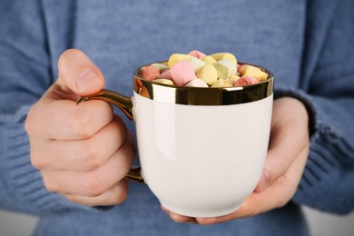 Woman holding cup of delicious hot chocolate with marshmallows, closeup