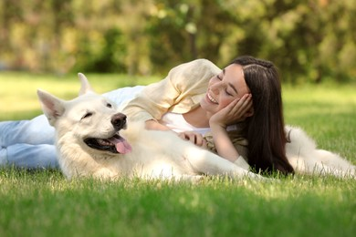 Teenage girl lying with her white Swiss Shepherd dog on green grass in park