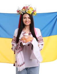Young woman in national clothes with traditional korovai and flag of Ukraine on white background