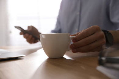 Man with cup of coffee at table indoors, closeup