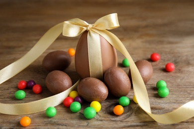 Tasty chocolate eggs and colorful candies on wooden table