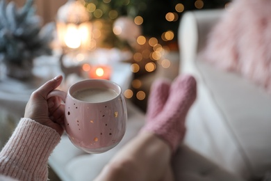 Woman holding cup of cocoa at home, closeup. Christmas mood