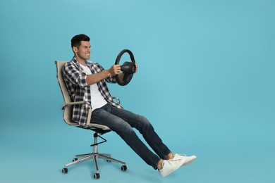 Happy man on chair with steering wheel against light blue background. Space for text