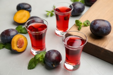 Delicious plum liquor, mint and ripe fruits on light table. Homemade strong alcoholic beverage