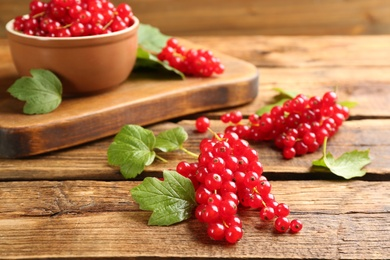 Delicious red currants and leaves on wooden table