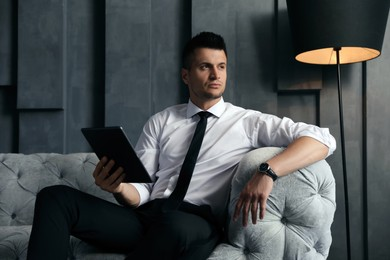 Handsome businessman with tablet on sofa indoors. Luxury lifestyle