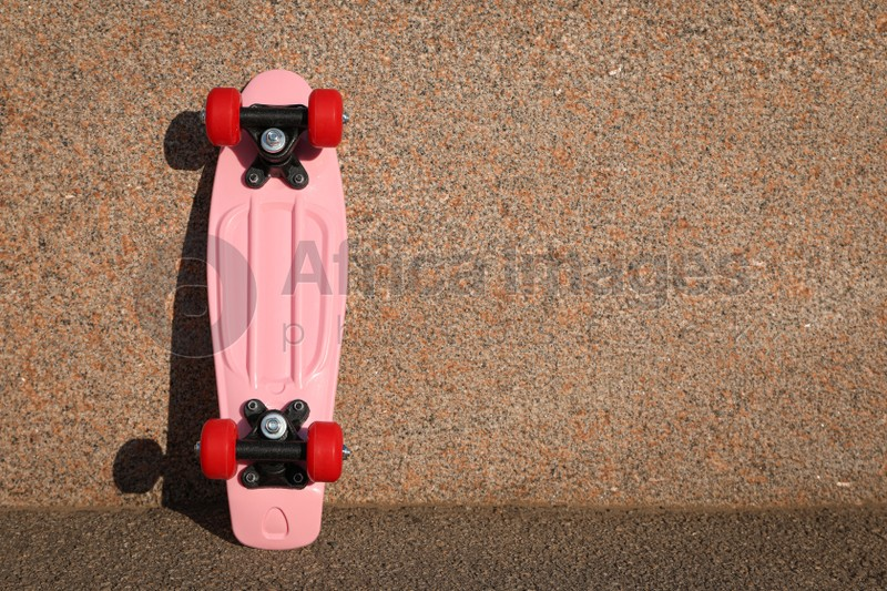 Pink skateboard with red wheels near wall outdoors. Space for text