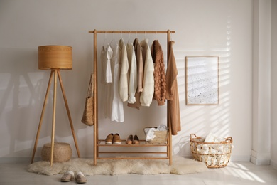 Modern dressing room interior with rack of stylish shoes and women's clothes