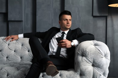 Handsome businessman with smartphone on sofa indoors. Luxury lifestyle