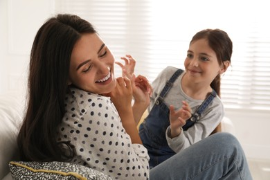 Happy single mother playing with her daughter in living room